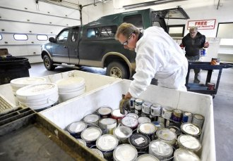 photo - At the El Paso County Household Hazardous Water facility, Chemical Waste Technician Harry Herriges stacks gallons of paint left by Britt Holstun (background) on Tuesday, November 22, 2016. If the paint is still usable, it will be set out on a shelf and given away to whoever gets it first. photo by Jerilee Bennett,The Gazette